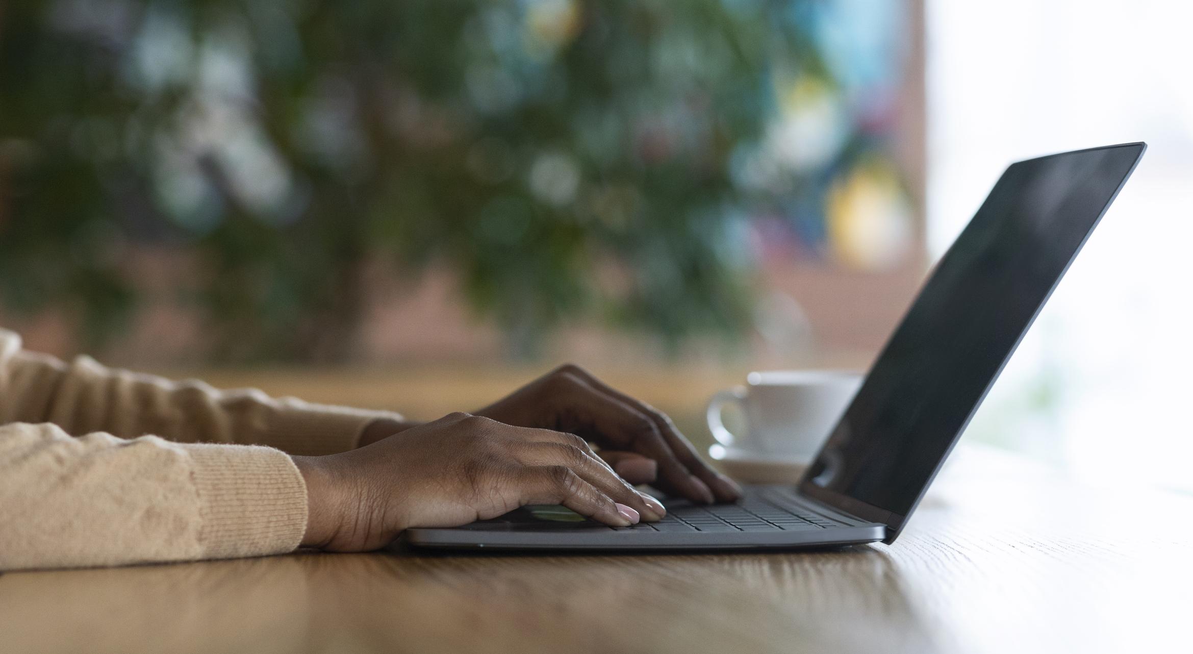 Hands of black girl typing on laptop keyboard, cafe interior